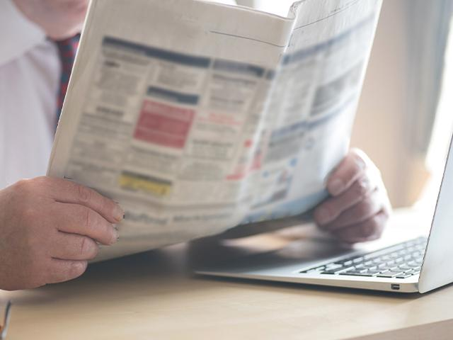 man looking at newspaper want ads