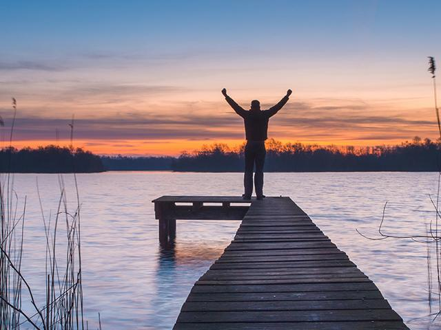 sunset, man on pier with raised arms, rejoice