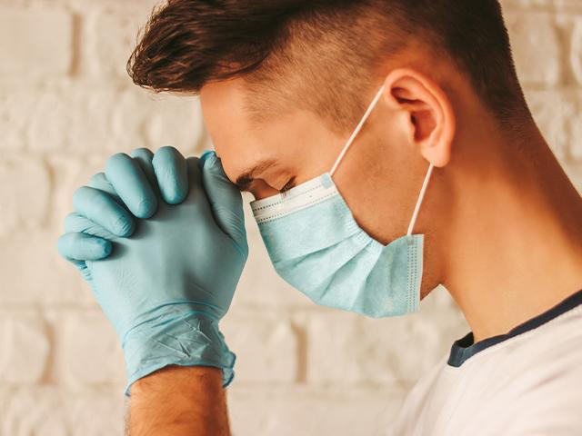 young man praying while wearing surgical mask and gloves