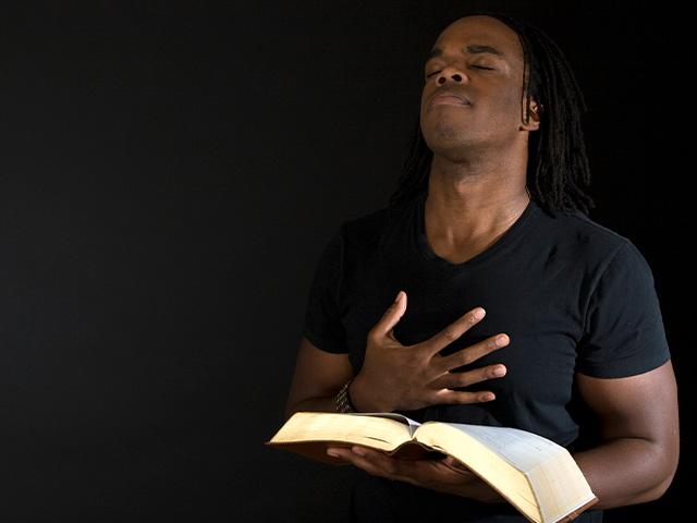 man reverencing God with his eyes closed and hand on his chest