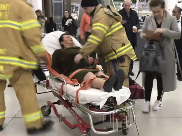 In this still image taken from video , emergency medical personnel tend to an injured passenger from a Turkish Airlines flight at New York's John F. Kennedy International Airport, Saturday, March 9, 2019.(WNBC-TV News 4 New York via AP)