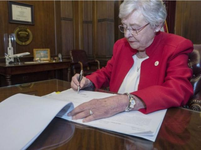 This photograph released by the state shows Alabama Gov. Kay Ivey signing a bill that virtually outlaws abortion in the state on Wednesday, May 15, 2019, in Montgomery, Ala. (Hal Yeager/Alabama Governor's Office via AP)