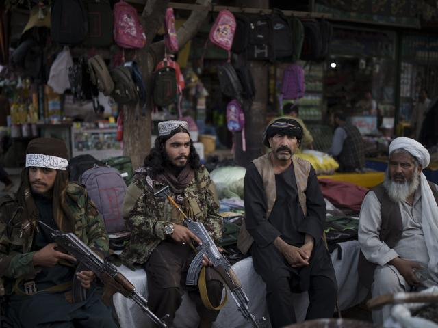 Taliban fighters sit next to street vendors at a local market in Kabul, Afghanistan