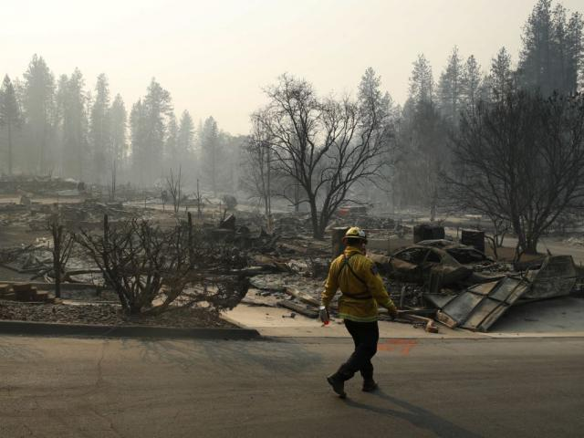 A firefighter searches for human remains in a trailer park destroyed in the Camp Fire, Friday, Nov. 16, 2018, in Paradise, Calif. AP Photo.