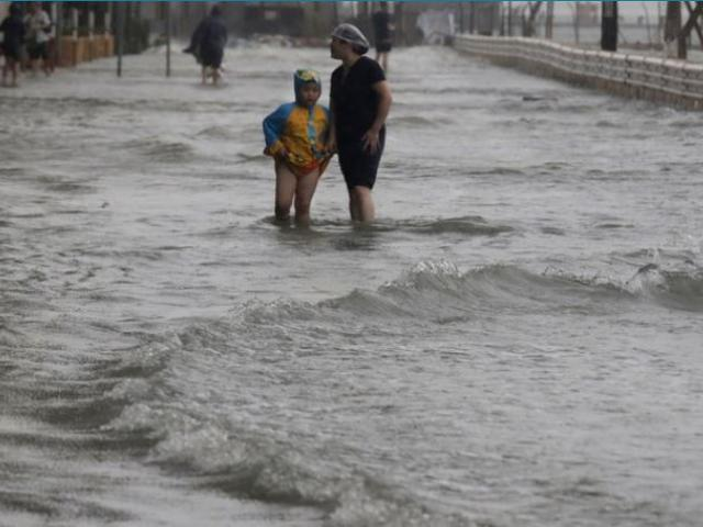People walk through floodwaters caused by Typhoon Mangkhut on the waterfront in Hong Kong on Sunday.  AP Photo.