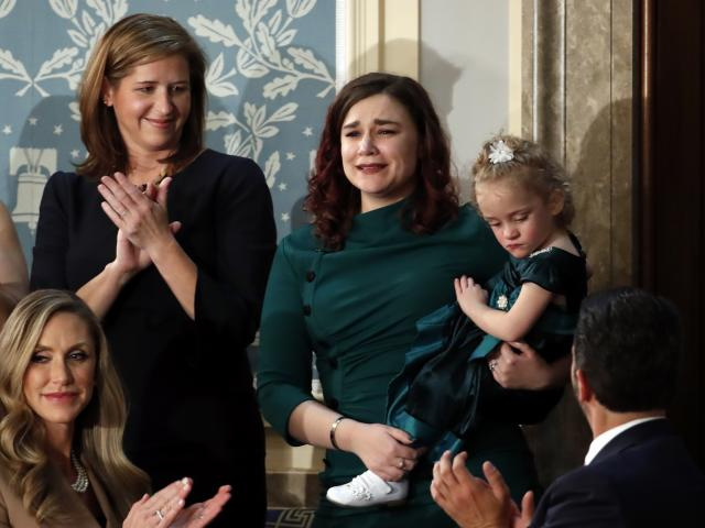 Robin Schneider of Kansas City, Mo., holds her daughter Ellie as President Donald Trump recognizes them during his State of the Union address, Feb. 4, 2020. (AP Photo/Alex Brandon)
