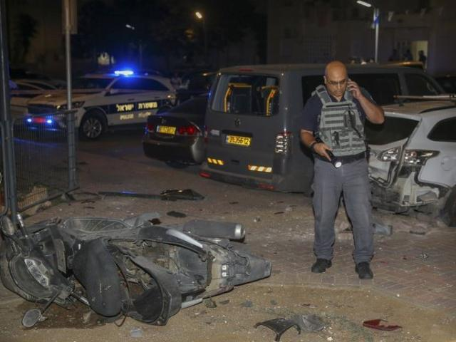 Israeli security stands at the site where a rocket from the Gaza Strip hit the town of Sderot, Photo, AP
