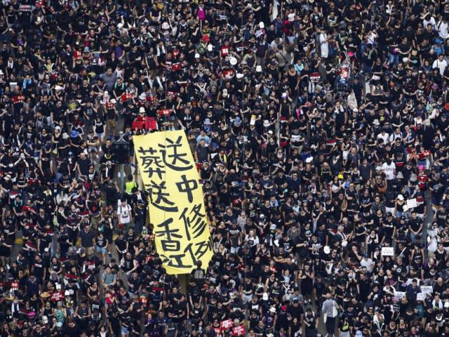 Tens of thousands of protesters carry posters and banners march through the streets as they continue to protest an extradition bill, Sunday, June 16, 2019, in Hong Kong. (Apple Daily via AP)