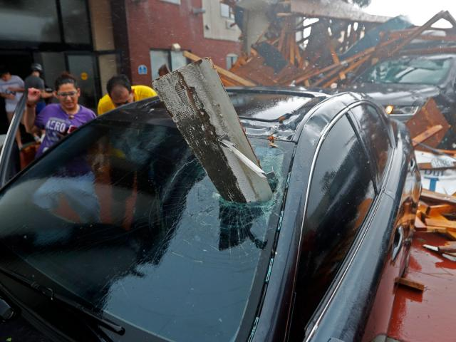 A woman checks on her vehicle as Hurricane Michael passes through, after the hotel canopy had just collapsed in Panama City, Florida, Wednesday. AP Photo.