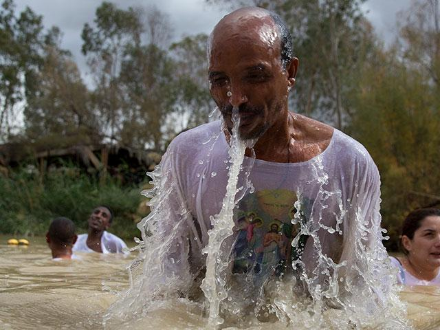 Members of the Eritrean and Ethiopian Christian Orthodox community baptized in the waters of the Jordan River during a baptism ceremony as part of the Orthodox Feast of the Epiphany at Qasr el Yahud