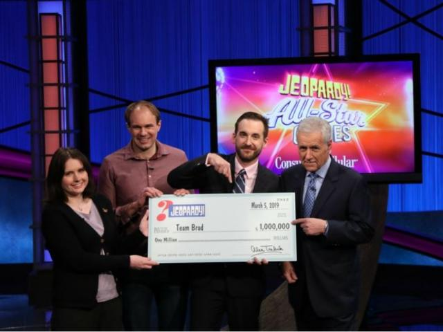 """This photo provided by Sony shows Brad Rutter, Larissa Kelly and David Madden with Alex Trebek, winners of the first-ever """"Jeopardy!"""" team championship, Tuesday, March 5, 2019 in in Burbank, Calif. (Carol Kaelson /Sony via AP)"""