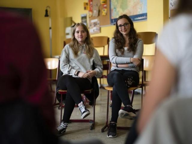 Laura Schulmann, center left, and Sophie Steiert, center right, listen to questions from students about Jewish daily life in Germany during the lesson as part of a project about religions at the Bohnstedt Gymnasium high school in Luckau, Germany.