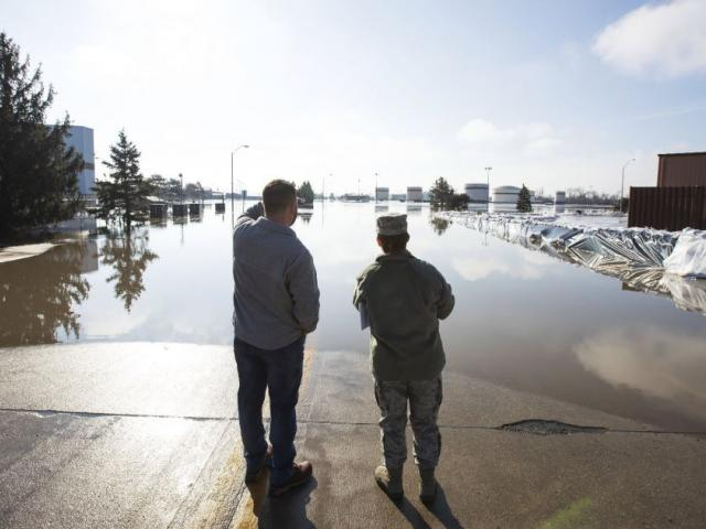 Luke Thomas and Air Force Tech Sgt. Vanessa Vidaurre look at a flooded portion of Offutt Air Force Base Sunday, March 17, 2015, in Bellevue, Neb.  (Z Long/Omaha World-Herald via AP)