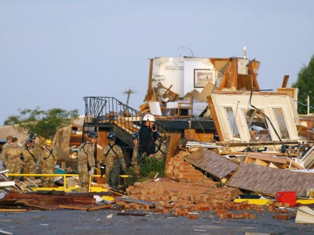 Workers look through tornado damage at the American Budget Value Inn in El Reno, Okla., Sunday, May 26, 2019. The deadly tornado leveled a motel and tore through the mobile home park near Oklahoma City overnight. (Bryan Terry/The Oklahoman via AP)