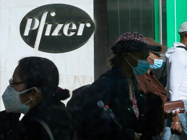 Pedestrians walk past Pfizer world headquarters in New York on Monday Nov. 9, 2020. (AP Photo/Bebeto Matthews)
