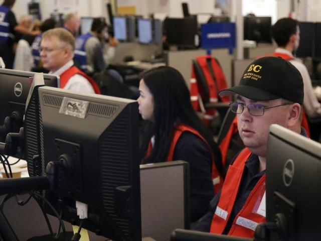 In this Oct. 10, 2019, file photo, Pacific Gas & Electric employees work in the PG&E Emergency Operations Center in San Francisco. (AP Photo/Jeff Chiu, File)
