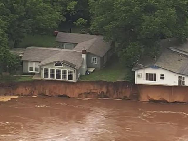 This image taken from video provided by KOCO-5 shows homes dangerously close to the Cimarron River on Wednesday, May 22, 2019 near Crescent, Okla. (KOCO-5 via AP)