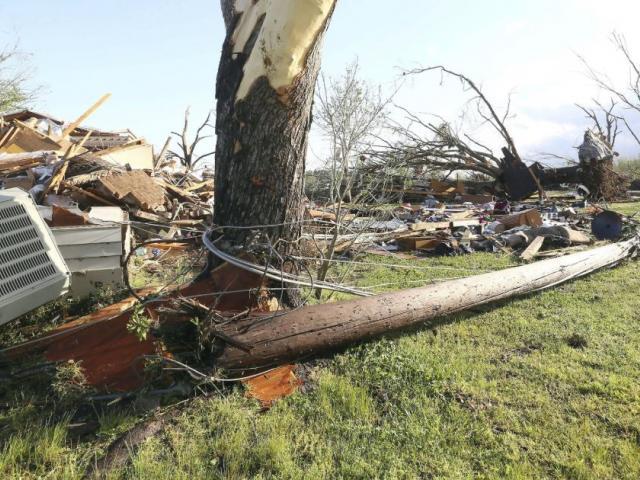 In this image made with a wide angle lens, debris is littered on the ground where a home once stood in Hamilton, Miss., after a deadly storm moved through the area Sunday, April 14, 2019. (AP Photo/Jim Lytle)