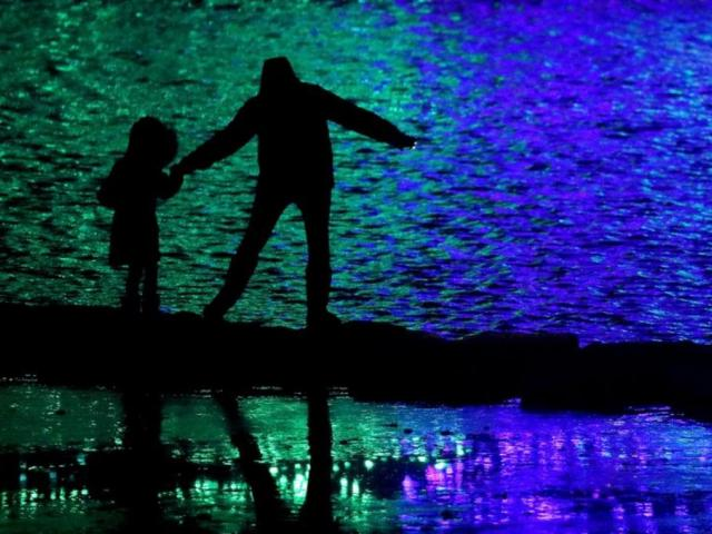In this Nov. 30, 2018, file photo people are silhouetted against holiday lights reflecting off a pond in a park in Lenexa, Kan. (AP Photo/Charlie Riedel, File)