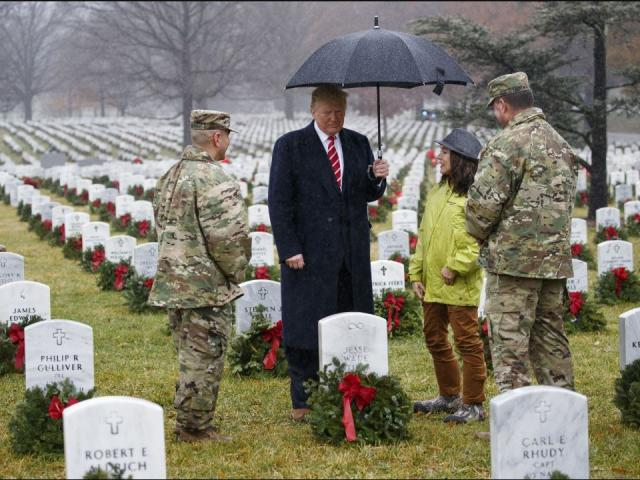 President Donald Trump pauses in the rain among holiday wreaths at graves at Arlington National Cemetery in Arlington, Va., Saturday, Dec. 15, 2018, during Wreaths Across America Day. AP photo.