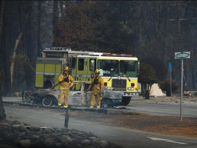 First responders watch as the motorcade of President Donald Trump visits a neighborhood impacted by the wildfires, Saturday, Nov. 17, 2018, in Paradise, Calif. AP Photo.