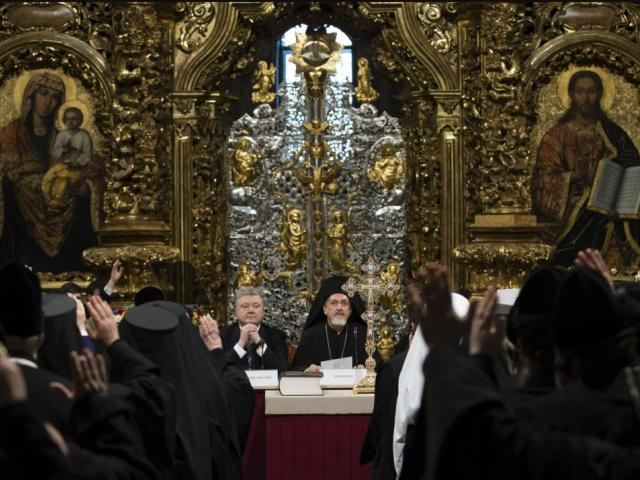 Ukrainian President Petro Poroshenko, center left, attends a closed-door synod of three Ukrainian Orthodox churches to approve the charter for a unified church and to elect leadership in the St. Sophia Cathedral in Kiev, Ukraine. AP file photo.