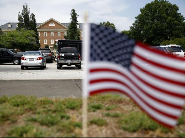 An American flag that is part of a makeshift memorial stands at the edge of a police cordon in front of a municipal building that was the scene of a shooting, Saturday, June 1, 2019, in Virginia Beach, Va. (AP Photo/Patrick Semansky)