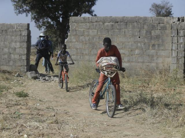 Image Source: Children ride on bicycles past a wall broken by Boko Haram who kidnapped students from their school (AP Photo/Sunday Alamba)