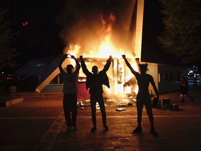Protestors raise their hands in front of a burning vending cart on May 29, 2020, in Atlanta, Georgia (Be Gray/Atlanta Journal-Constitution via AP)