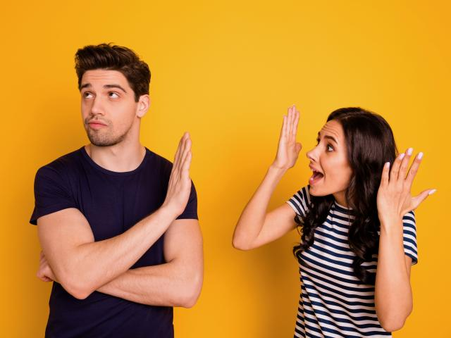 Annoyed fighting couple on bright yellow background
