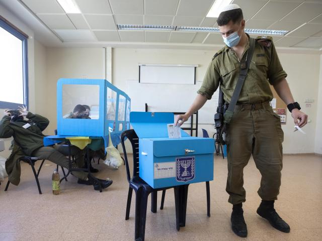 An Israeli soldier casts an early vote at an army base near the Arab town of Kafr Qara, in central Israel, Wednesday, March 17, 2021. Israel will be holding its fourth parliamentary election in two years on March 23. (AP Photo/Sebastian Scheiner)