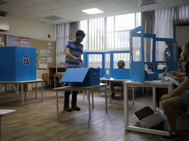 A man votes for Israel's parliamentary election at a polling station in Tel Aviv, Israel, Tuesday, March. 23, 2021. Israel is holding its fourth election in less than two years. (AP Photo/Sebastian Scheiner)