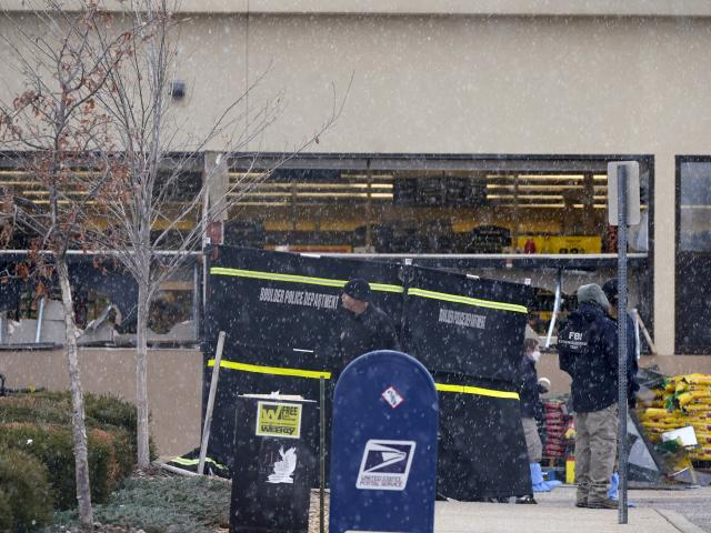 Snow falls as investigators continue to collect evidence in the parking lot where a mass shooting took place at a King Soopers grocery store Tuesday, March 23, 2021, in Boulder, Colo. (AP Photo/David Zalubowski)