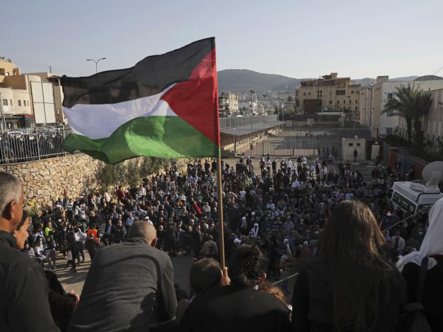 A Palestinian flag flies over the annual Land Day rally in the Arab city of Arraba, northern Israel, Tuesday, March 30, 2021. (AP Photo/Mahmoud Illean)
