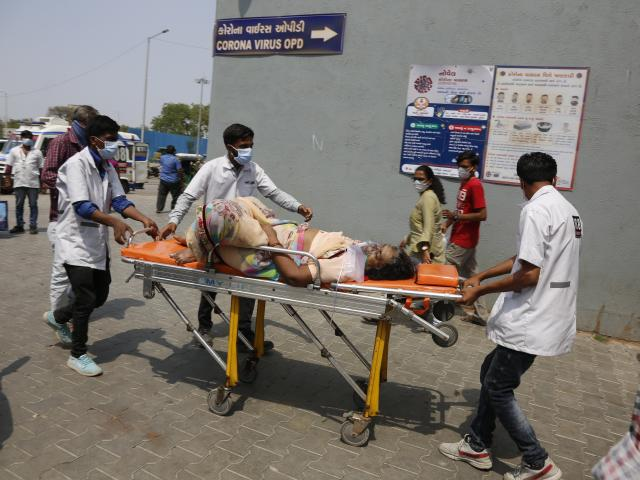 In this April 27, 2021, file photo, health workers bring a patient to be admitted at a government COVID-19 hospital in Ahmedabad, India. (AP Photo/Ajit Solanki, File)
