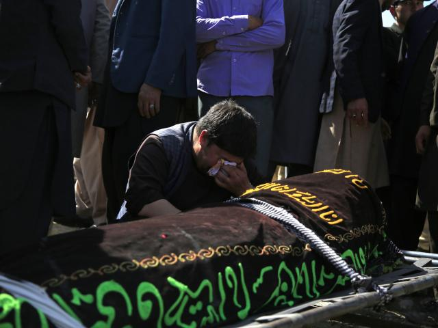 A man cries over the body of a victim of deadly bombings on Saturday near a school, at a cemetery west of Kabul, Afghanistan, Sunday, May 9, 2021.(AP Photo/Mariam Zuhaib)