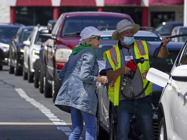 A customer helps pumping gas at Costco, as other wait in line, on Tuesday, May 11, 2021, in Charlotte, N.C. (AP Photo/Chris Carlson)