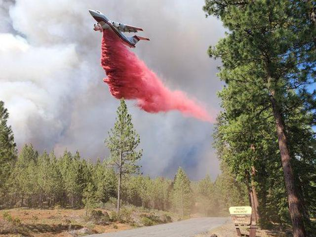 In this photo provided by the Bootleg Fire Incident Command, a tanker drops retardant over the Mitchell Monument area at the Bootleg Fire in southern Oregon on Saturday, July 17, 2021.  (Bootleg Fire Incident Command via AP)