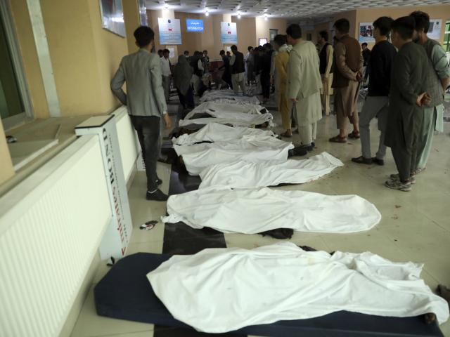 In this May 8, 2021 file photo, Afghan men try to identify the dead bodies at a hospital after a bomb explosion near a school west of Kabul, Afghanistan. (AP Photo/Rahmat Gul, File)