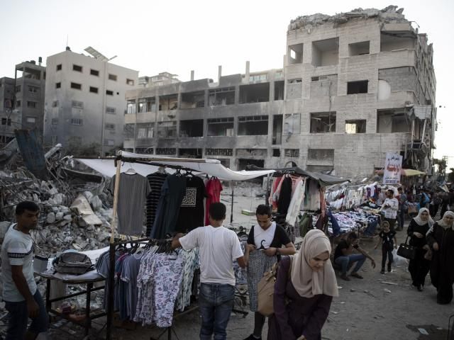In this Sunday, July 18, 2021, file photo, Palestinian street vendors display clothes for sale next to the rubble of destroyed buildings were hit by Israeli airstrikes during an 11-day war. (AP Photo/Khalil Hamra, File)