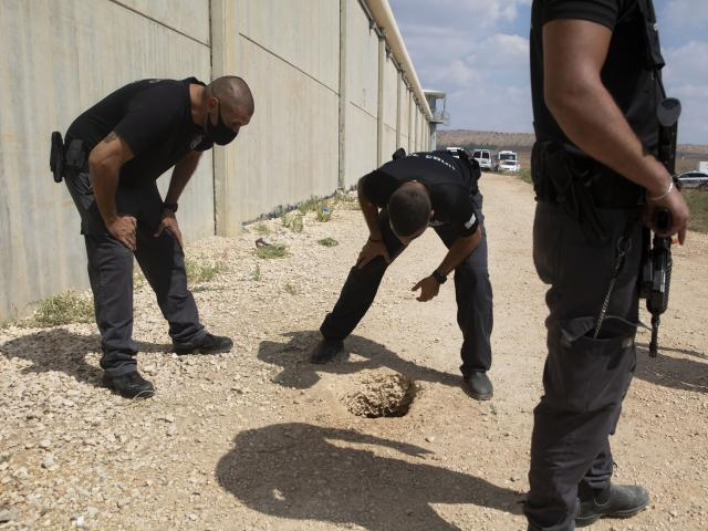 Police officers and prison guards inspect the scene of a prison escape outside the Gilboa prison in northern Israel, Monday, Sept. 6, 2021. (AP Photo/Sebastian Scheiner)