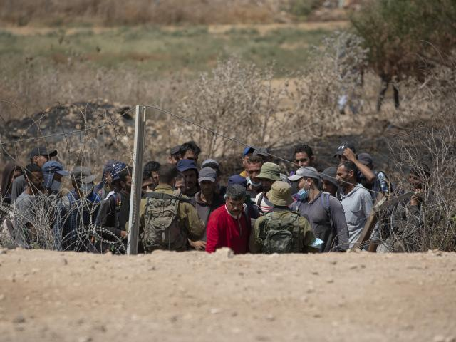Israeli troops carry out checks on Palestinian laborers returning home after a days work in Israel who are trying to cross through a damaged section of the Israeli separation fence, in the West Bank village of Jalameh, near Jenin, Monday, Sept. 6 (AP)