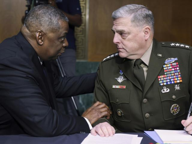 In this June 17, 2021 file photo, Secretary of Defense Lloyd Austin, left, and Chairman of the Joint Chiefs Chairman Gen. Mark Milley talk before a Senate Appropriations Committee hearing on Capitol Hill in Washington. (Evelyn Hockstein/Pool via AP)