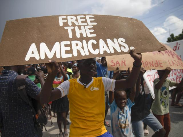 People protest for the release of kidnapped missionaries near the Ohio-based Christian Aid Ministries headquarters in Titanyen, north of Port-au-Prince, Haiti, Tuesday, Oct. 19, 2021. (AP Photo/Joseph Odelyn)