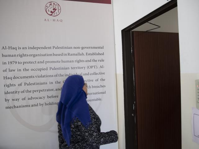A Palestinian women walks in the al-Haq human rights group organization's offices in the West Bank city of Ramallah, Saturday, Oct. 23, 2021.  (AP Photo/Majdi Mohammed)
