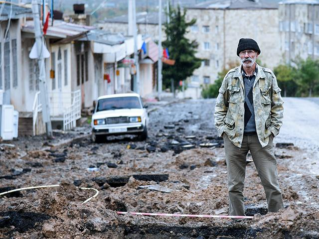 A man stands in a street damaged by shelling of Azerbaijan's artillery in Stepanakert, the self-proclaimed Republic of Nagorno-Karabakh, Azerbaijan, Tuesday, Oct. 6, 2020. (David Ghahramanyan/NKR InfoCenter PAN Photo via AP)