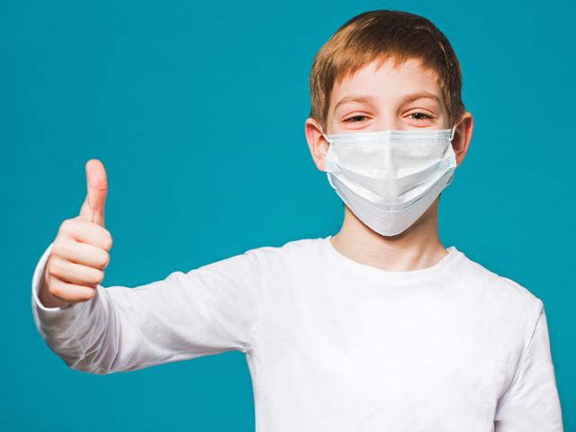Boy in surgical mask smiling