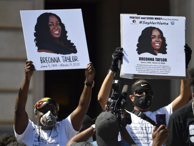 Signs are held up showing Breonna Taylor during a rally in her honor. (AP Photo/Timothy D. Easley, File)