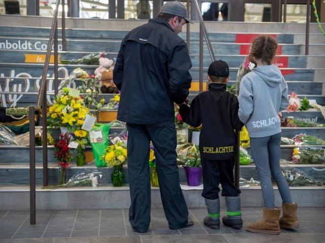 People pause at a memorial set up on the stairs of Elgar Petersen Arena in Humboldt, Saskatchewan, Canada. AP Photo.
