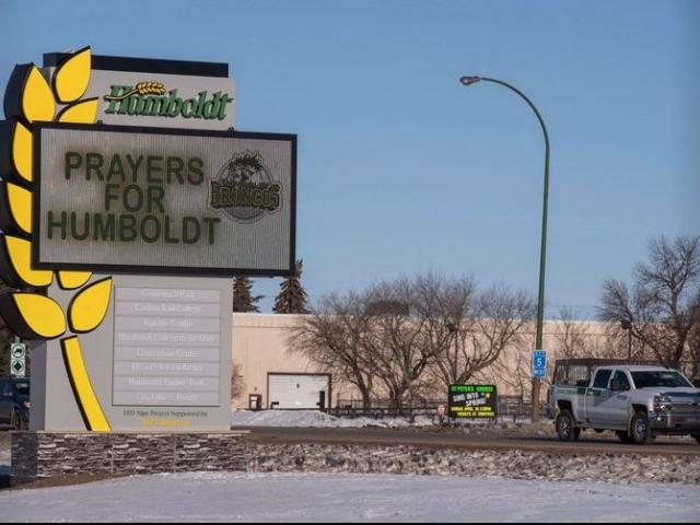 A truck drives by a sign honoring the members of the Humboldt Broncos hockey team in Humboldt, Saskatchewan, Canada.